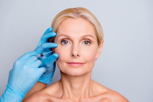 calm serious charming aged woman with wrinkle getting injection in cheek in professional clinic hands in gloves-img-blog
