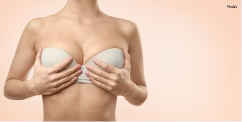 Women holding her breasts up to see how a breast lift would adjust breasts.