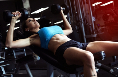 woman doing a dumbell chest press exercise.