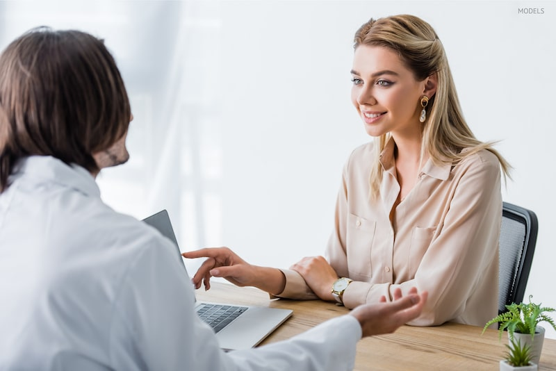 Woman pointing at a laptop during a consultation with her doctor.