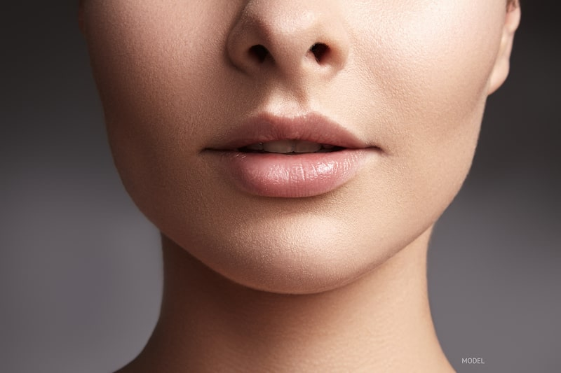 Close-up of woman's lips and chin against a gray background.